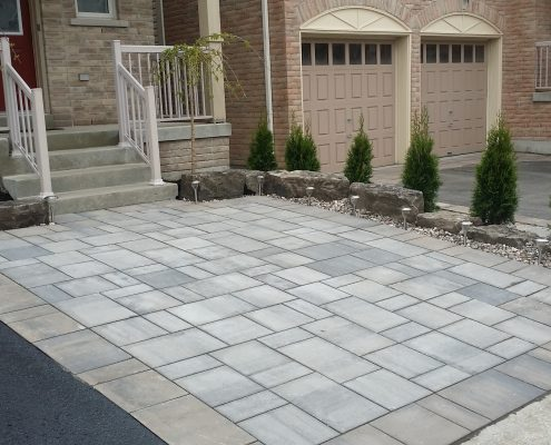 Interlocking driveway with armour stone retaining wall